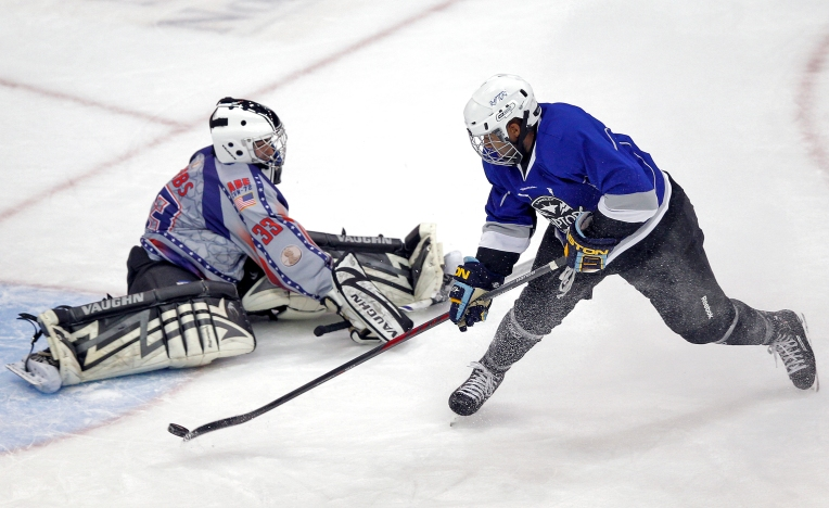 Langley Raptors' Roderick Johnson, right, shoots the puck past USS Abraham Lincoln goalie Stephen Dobbs during Saturday's Air vs. Sea hockey game at the Scope Arena in Norfolk on January 30, 2015.