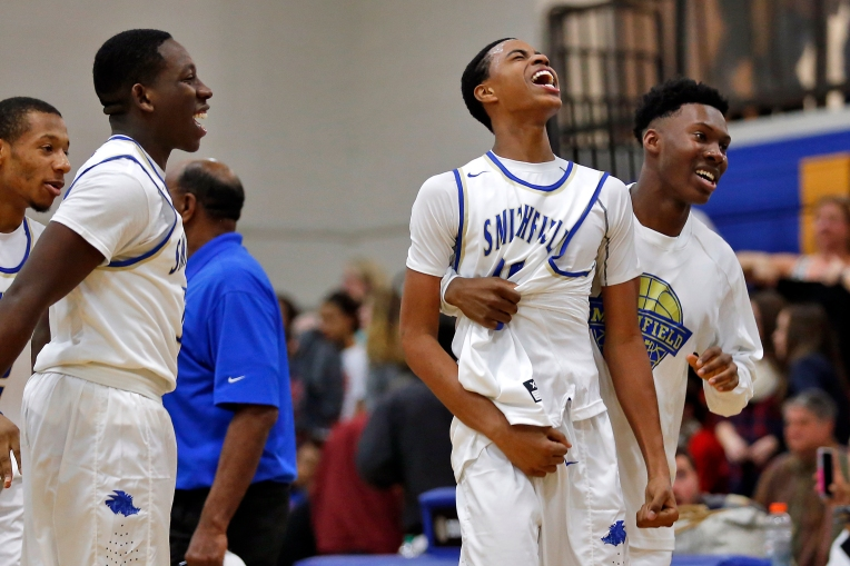 Smithfield's Keon Tucker, center, celebrates with teammates during Friday's game against Grafton's on January 8, 2015. Tucker made a three-point basket in the closing seconds to give the Packers a 50-49 lead.