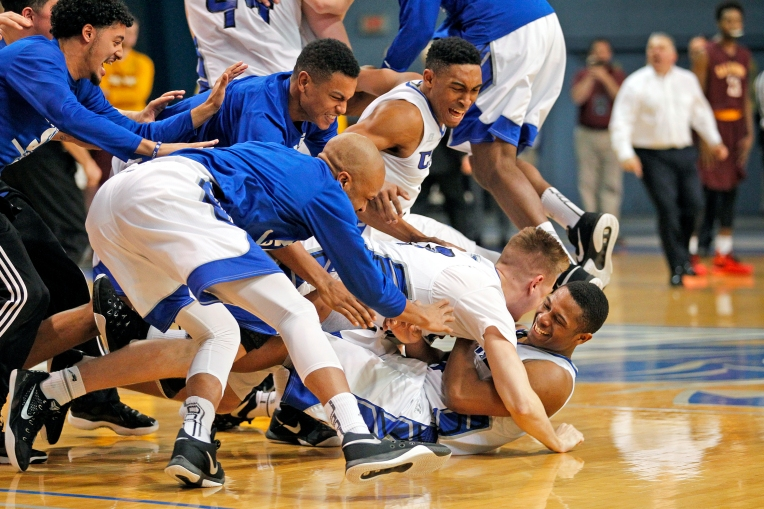 Christopher Newport University's Aaron McFarland, bottom right, is tackled to the floor by teammates as they celebrate defeating Salisbury 68-67 in overtime during Saturday's Capital Athletic Conference championship game at the Freeman Center on February 27, 2016.