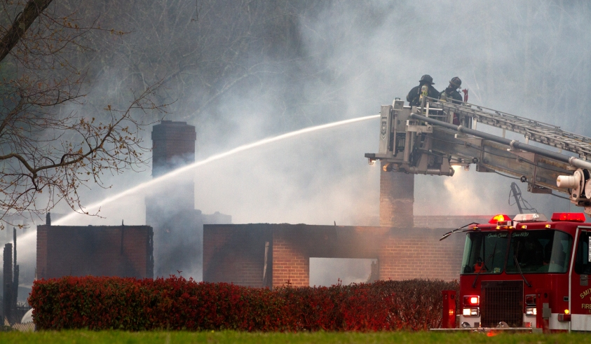 Firefighters douse the smoldering remains of an Isle of Wight home early Friday, March 25, 2016.