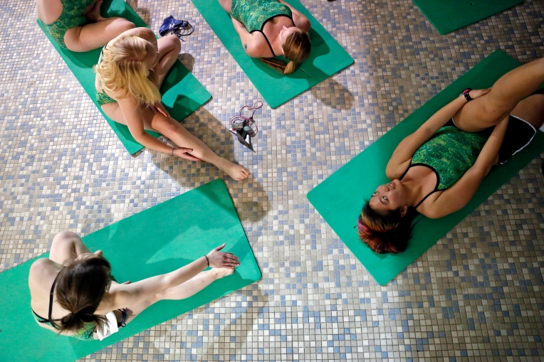 Cassandra Chang, right, and other members of William and Mary's synchronized swim club stretch before a practice at Adair Hall Thursday evening March 17, 2016. The team will be competing at the U.S. Collegiate Synchronized Swimming Championship March 24-26 at the University of Florida.
