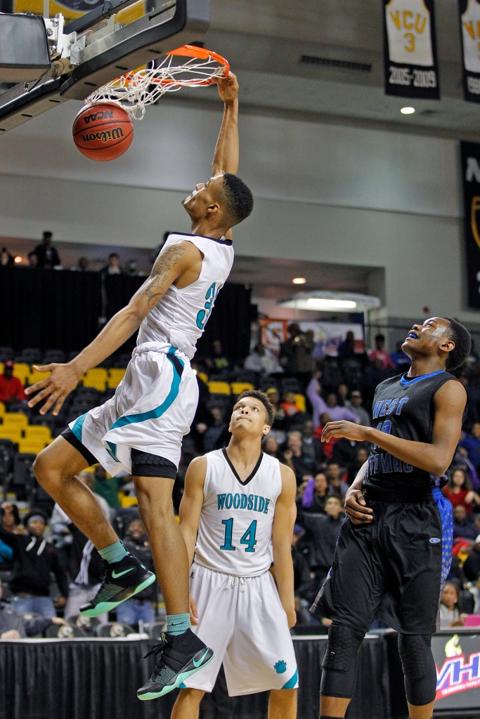 Woodside's Chris Orlina, left, slam dunks the ball over West Potomac's Daryl Mackey during Friday's 6A state quarterfinal at the Siegel Center on the campus of Virginia Commonwealth University.