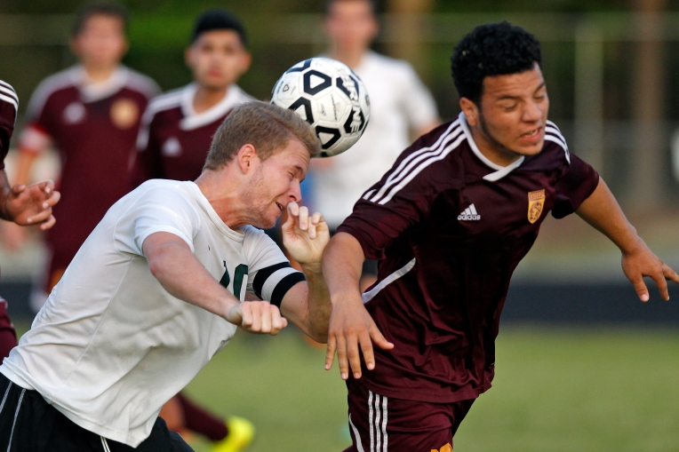 Kecoughtan's Brennen Burton, left, heads the ball past Warwick's Orly Villanueva-Moreno during Wednesday's Conference 10 semifinal on May 25, 2016.