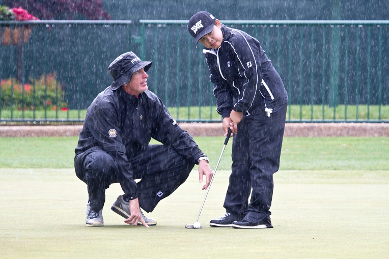 Coach Joe Hallte works with P.K. Kongkraphan on the putting green during heavy rain on Tuesday May 17, 2016 at Kingsmill in Williamsburg, Va.