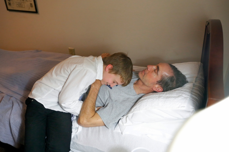 "Bradley Garner hugs his father, Jim, as he lays in bed at Commonwealth Assisted Living in Hampton Thursday evening March 24, 2016. Jim died from Alzheimer's April 2, 2016. Jim was diagnosed by the National Institute of Health in 2011 with ""mild cognitive impairment,"" the precursor to early-onset Alzheimer's disease. The genetically pre-determined disease has devastated his family--his mother died of the disease at age 61, his older brother at 52."