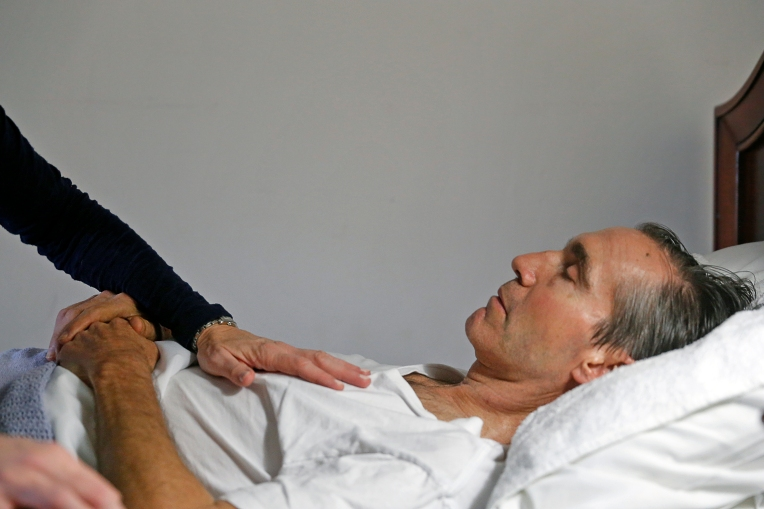 "Karen Garner comforts Jim as he lays in bed at Commonwealth Assisted Living in Hampton Saturday March 26, 2016. Jim died from Alzheimer's April 2, 2016. Jim was diagnosed by the National Institute of Health in 2011 with ""mild cognitive impairment,"" the precursor to early-onset Alzheimer's disease. The genetically pre-determined disease has devastated his family--his mother died of the disease at age 61, his older brother at 52."