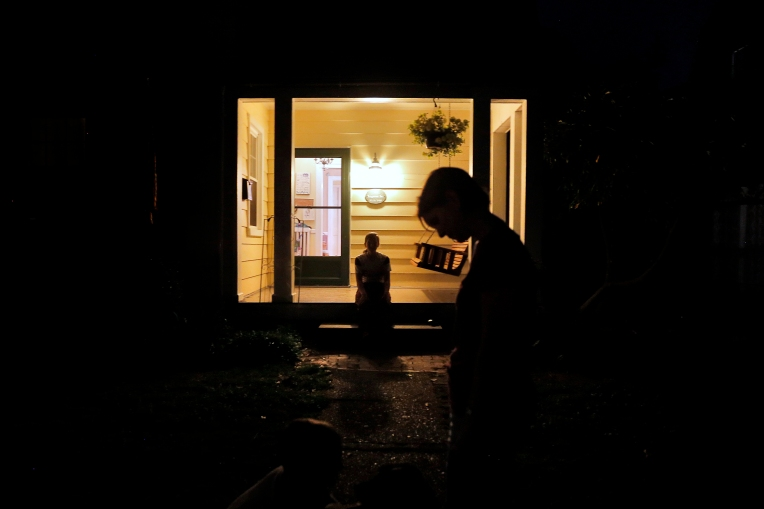 "Frankie Garner, center, sits on her porch as Karen Garner stands in front of their of house Tuesday evening April 26, 2016. Jim Garner died from Alzheimer's April 2, 2016. Jim was diagnosed by the National Institute of Health in 2011 with ""mild cognitive impairment,"" the precursor to early-onset Alzheimer's disease. The genetically pre-determined disease has devastated his family--his mother died of the disease at age 61, his older brother at 52."