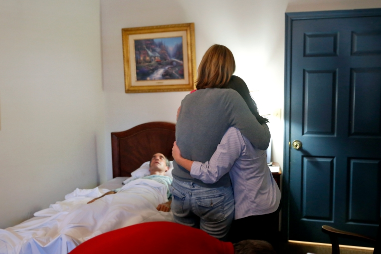 "Karen Garner is comforted by Shelly Simonds as Jim lays in bed at Commonwealth Assisted Living in Hampton Monday afternoon March 28, 2016. Jim died from Alzheimer's April 2, 2016. Jim was diagnosed by the National Institute of Health in 2011 with ""mild cognitive impairment,"" the precursor to early-onset Alzheimer's disease. The genetically pre-determined disease has devastated his family--his mother died of the disease at age 61, his older brother at 52."