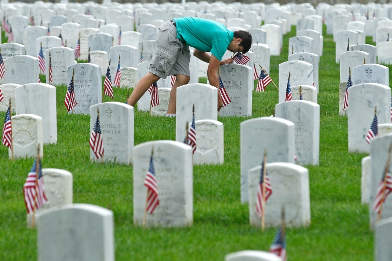 Austin Poe rearranges flags in front of gravestones at Hampton National Cemetery before the start of Monday's Memorial Day Ceremony on May 30, 2016.