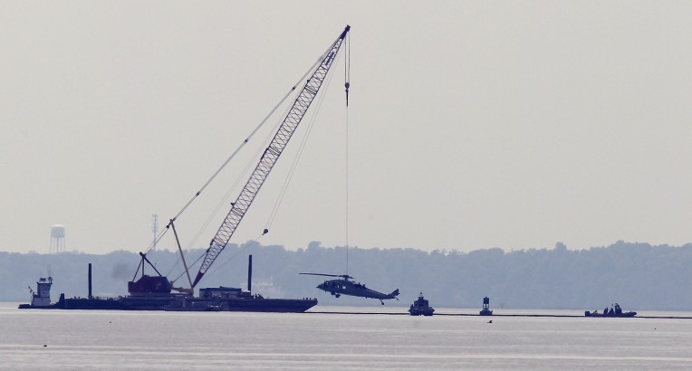 The wreckage of a Navy MH-60 helicopter is lifted out of the James River west of the James River Bridge Wednesday June 15, 2016. The helo crashed yesterday with no injuries to the crew.