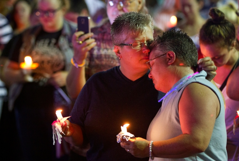 Kris and Cathy Johnson hold each other during a moment of silence during a vigil outside WHRO in Norfolk for the victims of the mass shooting in Orlando, Fl. on Sunday June 12, 2016.