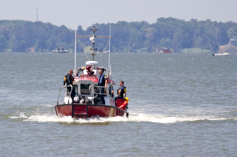 A Newport News Fire Department boat brings ashore three passengers that were aboard a Navy helicopter after it crashed into the James River Tuesday, June 14, 2016.