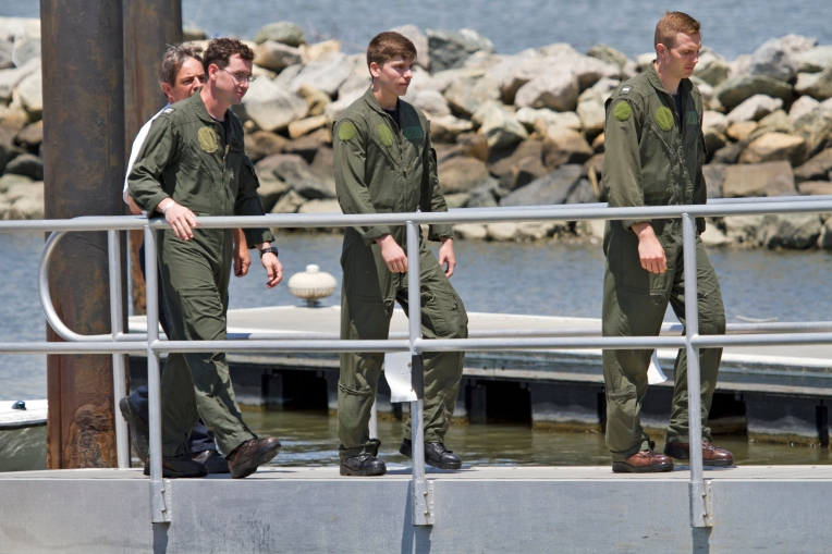 Three passengers that were aboard a Navy helicopter that crashed into the James River walk off a boat ramp at Huntington Park Tuesday, June 14, 2016.