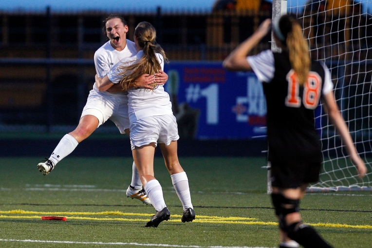 Tabb's Vita Sconyers, left, celebrates with Abby Jurewicz, center, after scoring in overtime to defeat Brentsville District during Thursday's 3A East Region semifinal on June 2, 2016.
