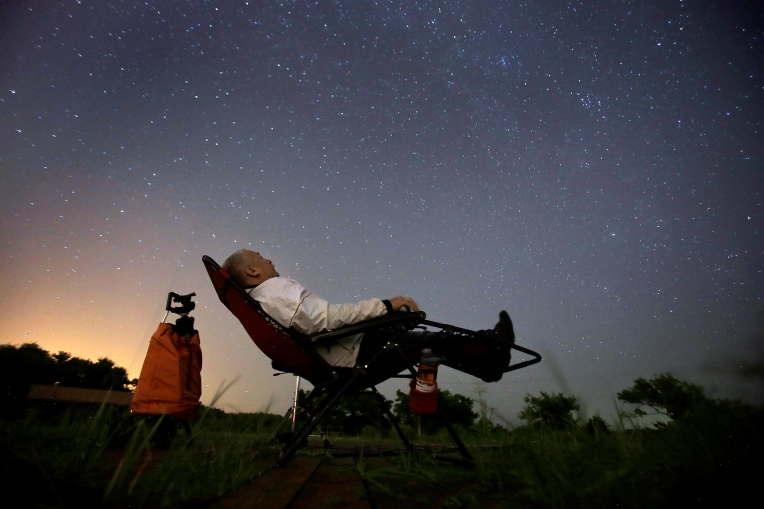 "Lawrence ""Bird"" Taylor sits in a chair watching the sky while waiting to see the Perseid meteor shower early Friday morning August 12, 2016. Members of the Virginia Peninsula Astronomy/Stargazers gathered at Grundland Creek Park in hopes of seeing meteors."