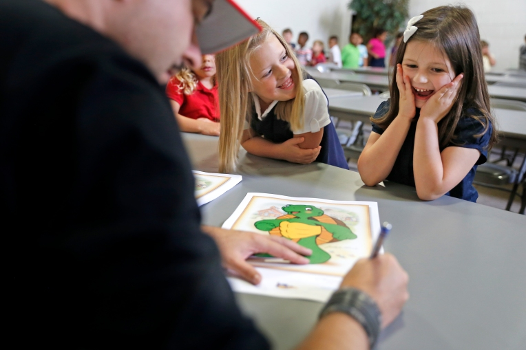 Noelle Chapell, left, and Sophie Simmons, right, react as children's illustrator Kurt Lehner signs a lithograph for the Warwick River Christian School students Thursday morning September 8, 2016. Lehner taught the students about illustration and demonstrated how to draw Franklin the Turtle.