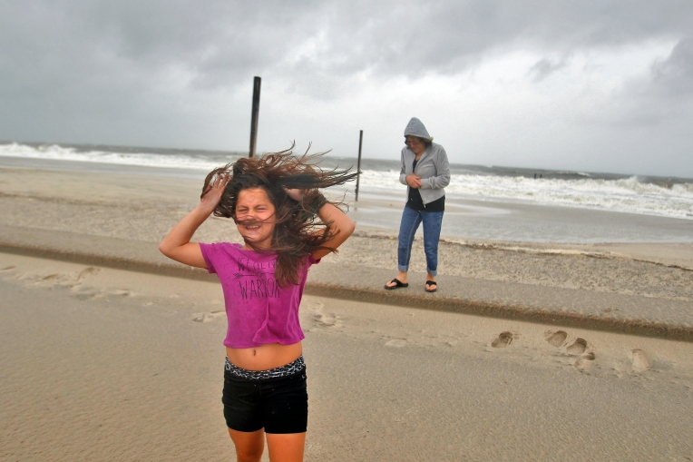 Victoria Cieremans covers her face as high winds move through Buckroe Beach Saturday morning September 3, 2016.