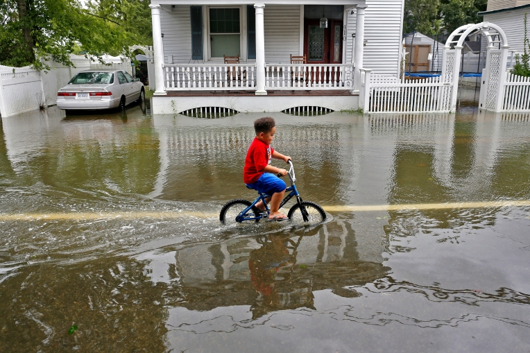 Brandon Durand bikes through flooded waters along Pembroke Avenue Saturday afternoon September 3, 2016.