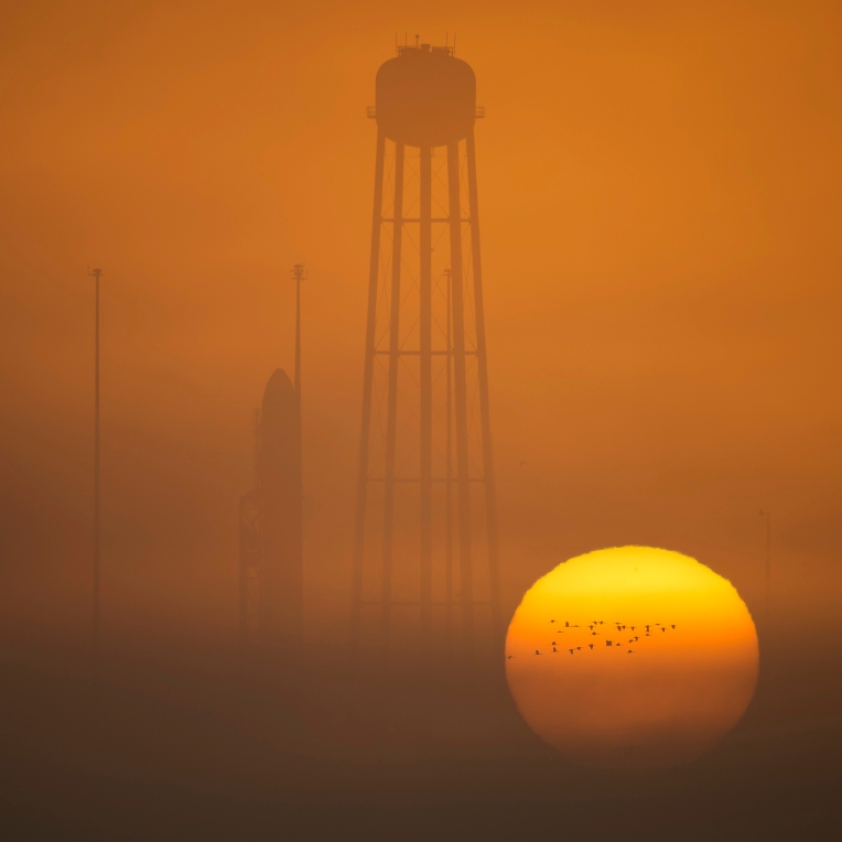 In this photo provided by NASA, the Orbital ATK Antares rocket, with the Cygnus spacecraft onboard, sits on launch Pad-0A during sunrise, Sunday, Oct. 16, 2016, at NASA's Wallops Flight Facility in Virginia. The Sunday scheduled cargo resupply mission to the International Space Station would be the company's first Antares launch since an explosion seconds after liftoff in 2014, which destroyed the rocket and space station supply ship, and damaged the launch complex. (Bill Ingalls/NASA via AP)