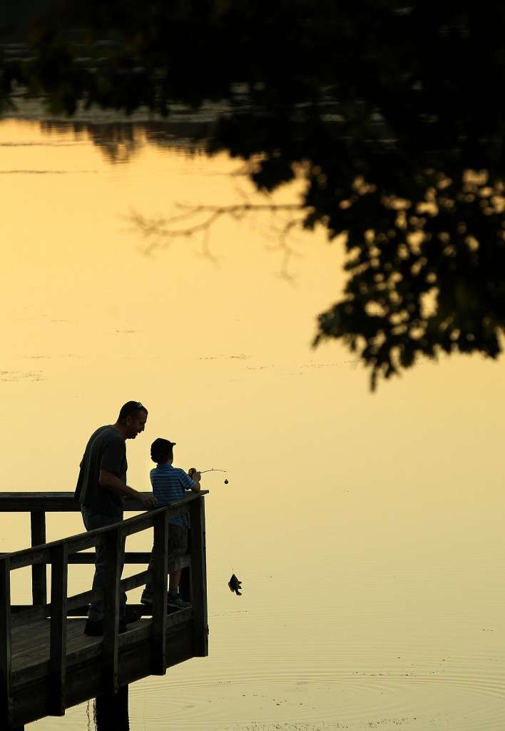 Mike Loudin coaches his son A.J. as he pulls a small sunfish for the lake at Newport News Park Tuesday evening.