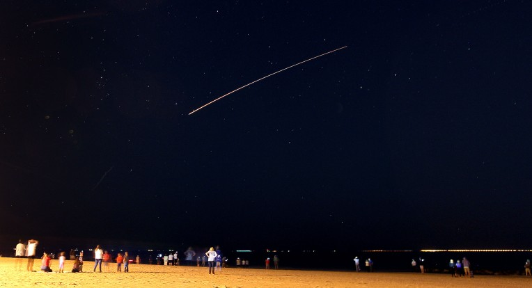 The Chesapeake Bay Bridge Tunnel is visible from Buckroe Beach as Orbital ATK's unmanned Antares rocket streaks out over the ocean after a successful launch from Wallops Flight Facility Monday October 17, 2016.