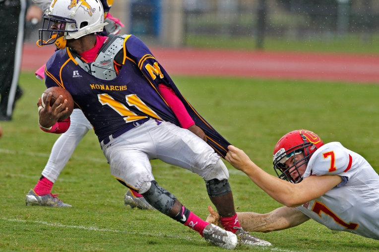 Menchville's Shemar Butts, left, is dragged down by Gloucester's Joseph Conroy during Saturday's game at Todd Stadium October 8, 2016.