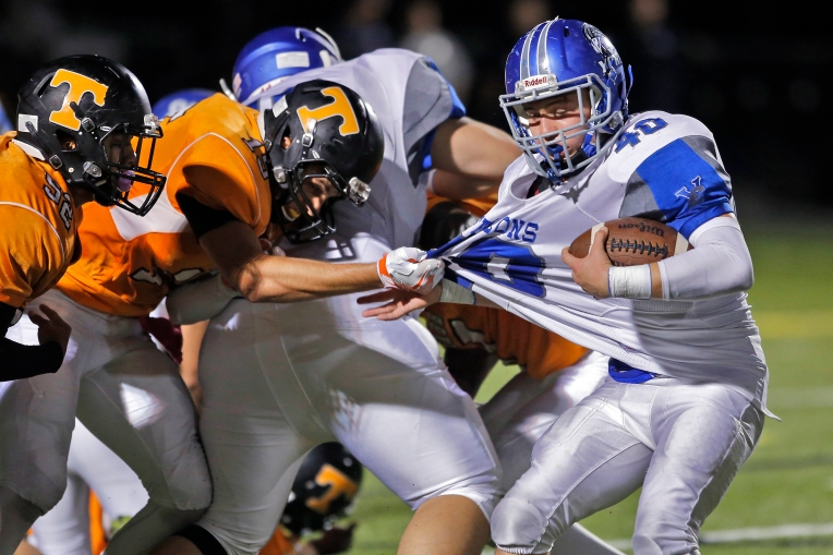 Tabb's Zach Wusk, left, grabs onto York's Noah Pascarella, right, during Friday's game at Bailey Field on October 14, 2016.