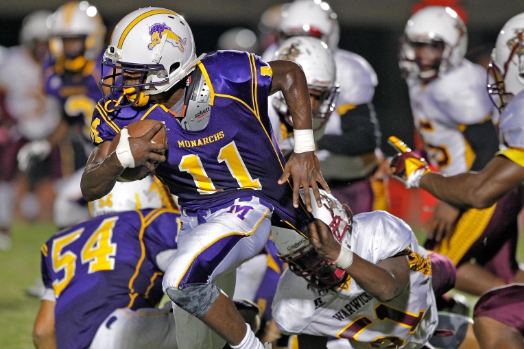 Menchville's Shemar Butts, left, is tackled by Warwick's Damone Davis during Saturday's game at Todd Stadium on October 1, 2016.