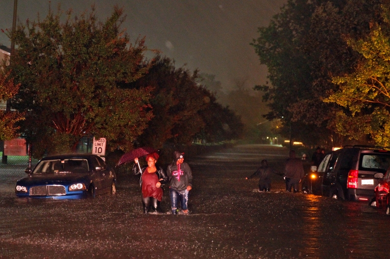 People walk through a flooded road near City Line Apartments near Lassiter Drive Saturday evening October 8, 2016.