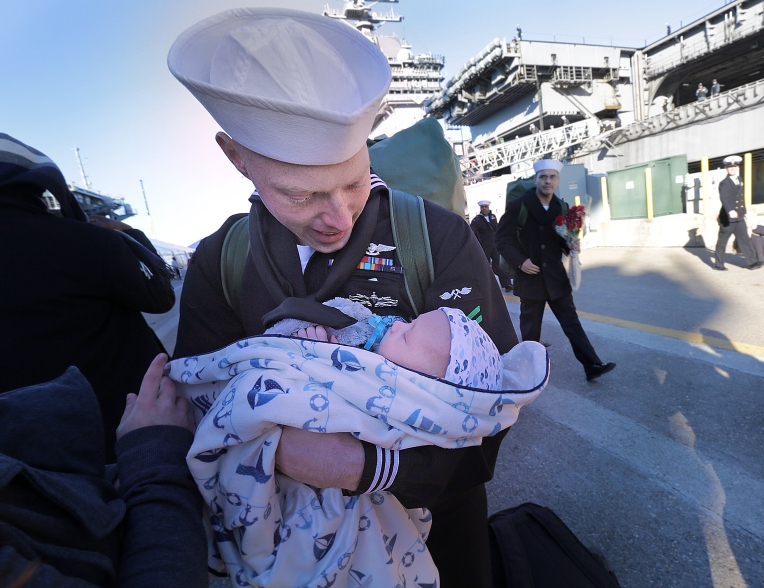 James Lee gazes at the face of his baby born while he was on deployment.The Eisenhower Carrier Strike Group returned to Norfolk Naval Station on Friday, December 30, 2016.