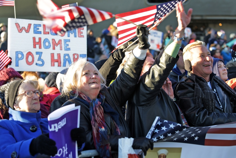 From left, Ellen Britton, Cathy Kyles, Marie Jackson, Tony Jackson wave at the sailors lining the deck hoping to catch the eye of a relative. The Eisenhower Carrier Strike Group returned to Norfolk Naval Station on Friday, December 30, 2016.