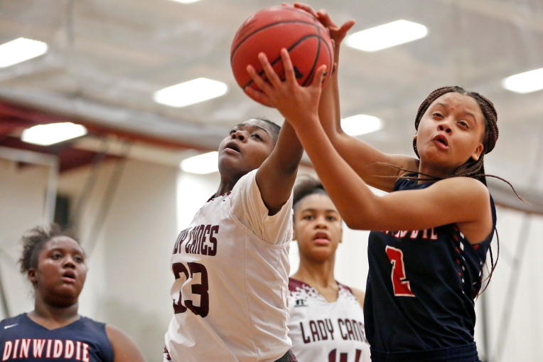 Heritage's Jordin Riddick, left, battles for control of the ball with Dinwiddie's Allyce Hayes during Wednesday's game December 21, 2016.