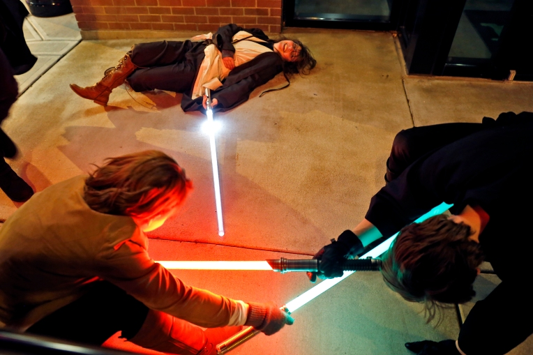 Genevieve Smith, center, watches as friends with lightsabers battle outside of Paragon Theater before the premiere of Rouge One: A Star Wars Story Thursday evening December 15, 2016.