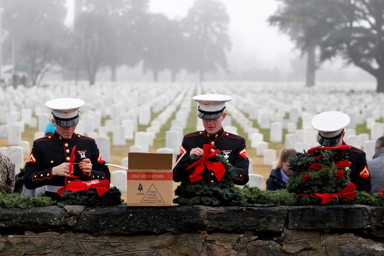 Lance Cpl. Richard Starkey, left, Lance Cpl. Carson Potter, center, and Lance Cpl. Connor Cross, right, prepare wreaths before the start of Saturday's ceremony for Wreaths Across America at Hampton National Cemetery December 17, 2016. Local military and volunteers gathered to participate in laying wreaths on the graves of the fallen.