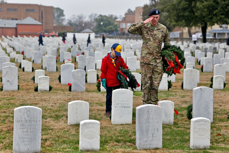 Dylan Cochran, left, watches as Pfc. Peter Demet, right, salutes after laying a wreath during Saturday's ceremony for Wreaths Across America at Hampton National Cemetery December 17, 2016. Local military and volunteers gathered to participate in laying wreaths on the graves of the fallen.
