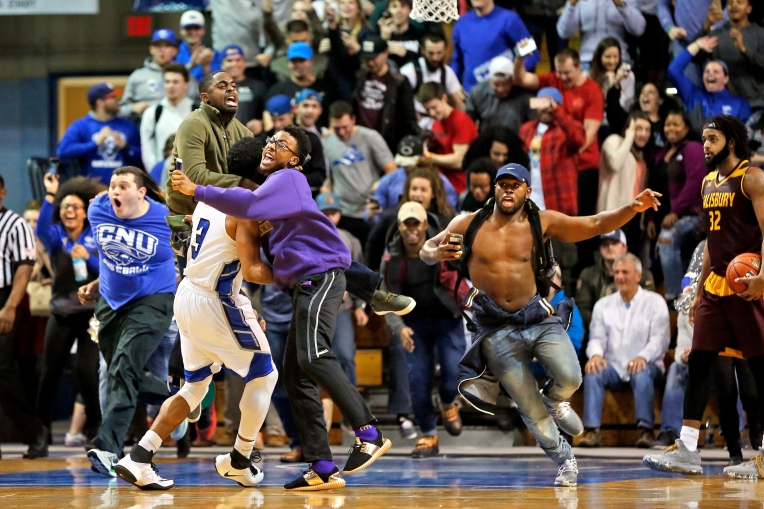 Fans run onto the court to celebrate with Christopher Newport University's Marcus Carter, left, after defeating Salisbury 55-53 during Wednesday's game at the Freeman Center January 25, 2017.