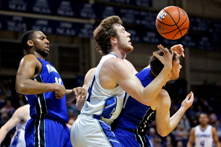 Christopher Newport University's Tim Daly, center, looks for a loose ball with Marymount's Dimitri Rucker, left, and Michael Anderson, right, during Wednesday's game at the Freeman Center February 8, 2017.