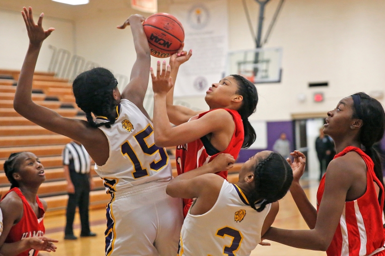 Hampton's Armani Franklin, center, attempts to shoot the ball around Menchville's Amari Carter, left, and Zhymani Smith during Thursday's game February 9, 2017.