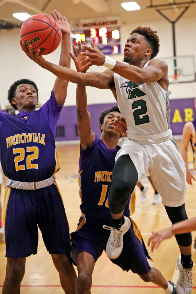 Kecoughtan's Keith Grandy, right, drives to the basket around Menchville's Ahmaad Goldson, left, and Amar Hawkins, center, during Tuesday's PenSouth Conference 10 quarterfinal February 14, 2017.