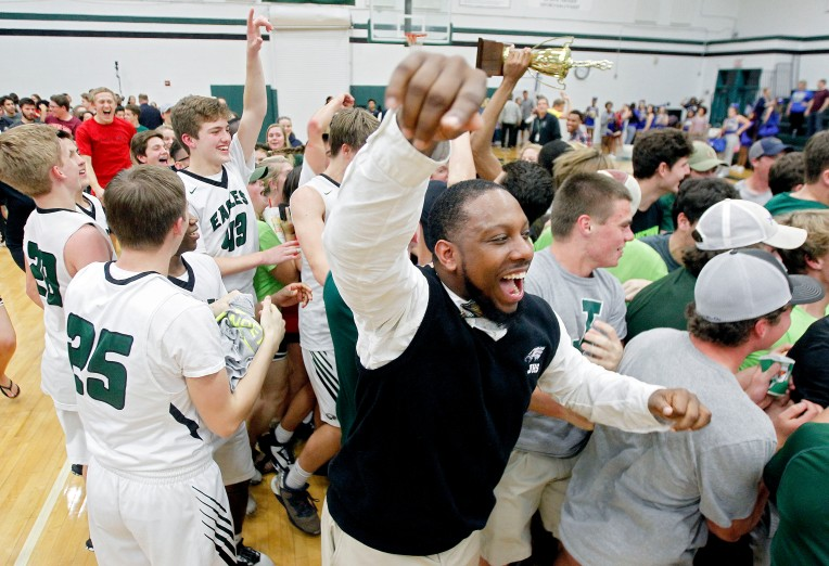 Jamestown coach Donovan Bridgeforth celebrates as students rush the court after defeating Smithfield 65-56 and winning 4A East Tournament Championship Friday February 24, 2017 at Jamestown.